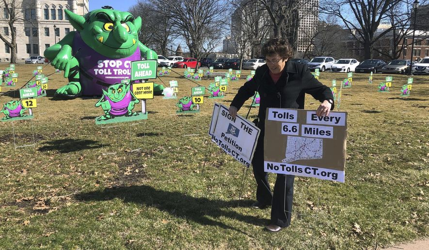 """Joanne Baker of Woodstock carries two signs showing her opposition to proposed tolls on Connecticut highways, Tuesday, March 19, 2019, outside the Connecticut State Capitol in Hartford, Conn. The conservative Yankee Institute for Public Policy erected a large """"Toll Troll"""" on the front lawn of the Capitol ahead of a planned committee vote on tolls. (AP Photo/Susan Haigh)"""