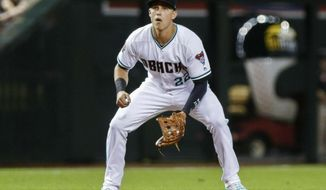 FILE - In this July 20, 2018, file photo, Arizona Diamondback' Jake Lamb plays third base against the Colorado Rockies during a baseball game in Phoenix. With key players still on the roster and new players who should fill at least some of the void, the Diamondbacks are hoping to compete for a playoff spot even with one of baseball's best players on a new team.(AP Photo/Darryl Webb, File)