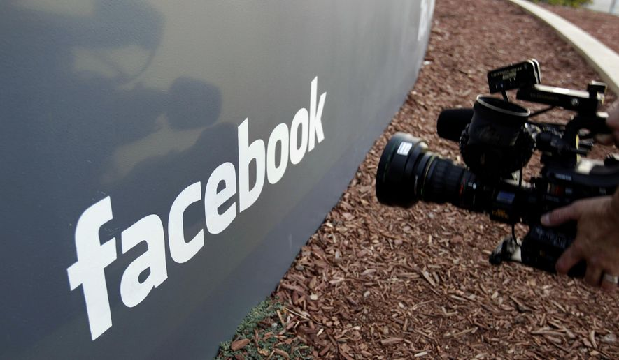 FILE- In this May 18, 2012, file photo a television photographer shoots the sign outside of Facebook headquarters in Menlo Park, Calif. Facebook has settled five lawsuits alleging that its advertising systems could be used to enable discrimination in housing, credit and employment ads, checking off one problem from its list of many. (AP Photo/Paul Sakuma, File)