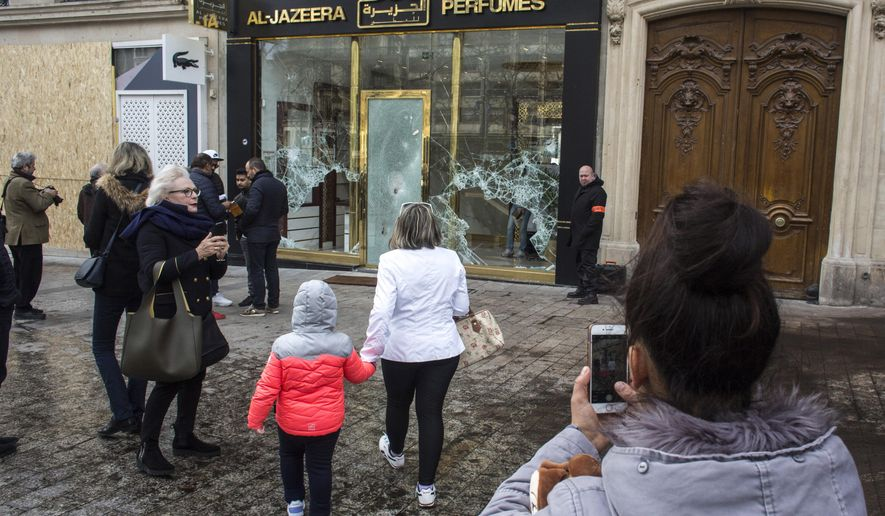 Bystanders take snapshots of a vandalized perfumery the day after riots erupted on the Champs Elysee avenue during the 18th straight weekend of demonstrations by the yellow vests in Paris, France, Sunday, March 17, 2019. Paris cleaned up one of the world's most glamorous avenues Saturday after resurgent rioting by yellow vest protesters angry at President Emmanuel Macron stunned the nation. (AP Photo/Rafael Yaghobzadeh)