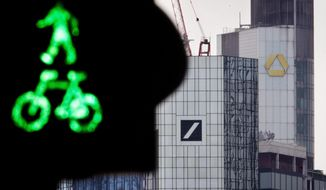 A traffic light stands in front of the headquarters of Deutsche Bank, left, and Commerzbank in Frankfurt, Germany, Monday, March 18, 2019. Deutsche Bank and Commerzbank begin talks on a possible merger. (AP Photo/Michael Probst)