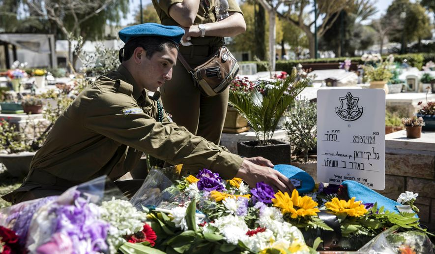 Israeli soldiers and friends of Staff Sgt. Gal Keidan mourn at his grave after the funeral in the city of Beersheba, Monday, March 18, 2019. Keidan was killed by Palestinian assailant in the West Bank Sunday. (AP Photo/Tsafrir Abayov)