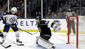 Winnipeg Jets' Kyle Connor, left, scores past Los Angeles Kings goaltender Jack Campbell, front right, during the first period of an NHL hockey game Monday, March 18, 2019, in Los Angeles. (AP Photo/Marcio Jose Sanchez)