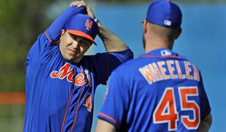 FILE - In this Feb. 14, 2019, file photo, New York Mets pitcher Jacob deGrom, left, talks with teammate Zack Wheeler while stretching during spring training baseball practice in Port St. Lucie, Fla. (AP Photo/Jeff Roberson, File)