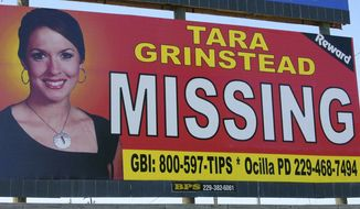 FILE - In this Wednesday, Oct. 4, 2006 file photo, missing teacher Tara Grinstead is displayed on a billboard in Ocilla, Ga. A Georgia man is standing trial on charges that he helped conceal the death of Tara Grinstead, who disappeared more than 13 years ago. Bo Dukes is charged with concealing a death, hindering the apprehension of a felon and lying to police after Tara Grinstead vanished from her home in rural Irwin County in October 2005. His trial began Monday, March 18, 2019. (AP Photo/Elliott Minor, File)