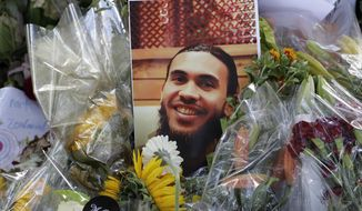 A photo tribute for Christchurch mosque shooting victim Tariq Omar lies amid mounds of flowers across the road from the Al Noor mosque in Christchurch, New Zealand Tuesday, March 19, 2019. (AP Photo/Mark Baker)