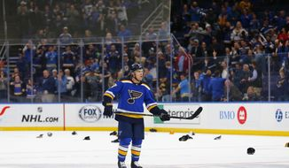 Fans throw their hats on the ice after St. Louis Blues' Jaden Schwartz (17) completed a hat trick against the Edmonton Oilers during the third period of an NHL hockey game Tuesday, March 19, 2019 in St. Louis. (AP Photo/Dilip Vishwanat)