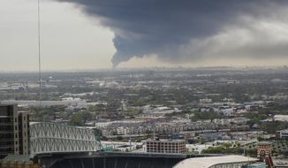 A plume of smoke from a petrochemical plant fire in Deer Park can be seen from the 31st floor of a downtown office building Monday, March 18, 2019, in Houston. The large fire at a Houston-area petrochemicals terminal will likely burn for another two days, authorities said Monday, noting that air quality around the facility was testing within normal guidelines. (Steve Gonzales/Houston Chronicle via AP)