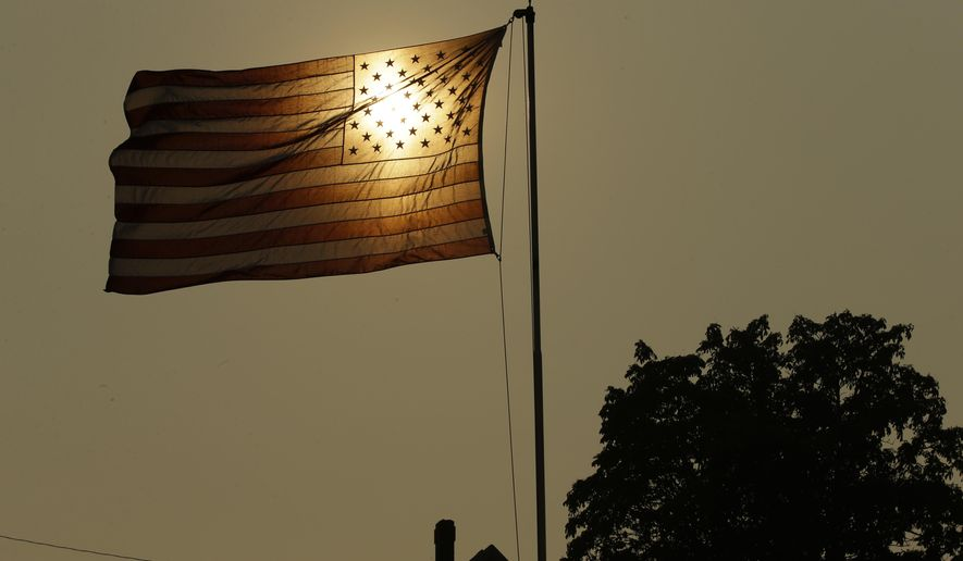 FILE - In this Aug. 2, 2017 file photo, the evening sun shines through a U.S. flag flying in the wind in Tacoma, Wash., against a sky made hazy with smoke from wildfires, as the National Weather Service issued an excessive heat warning for western Washington and Oregon. An AP data analysis of records from 1999-2019 shows that in weather stations across America, hot records are being set twice as often as cold ones. (AP Photo/Ted S. Warren, File)