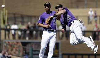 Colorado Rockies second baseman Ryan McMahon (24) throws to first as third baseman Nolan Arenado looks on after McMahon fielded a ground ball from Cincinnati Reds' Jesse Winker in the third inning of a spring training baseball game Monday, March 18, 2019, in Scottsdale, Ariz. Winker was out on the play. (AP Photo/Elaine Thompson)