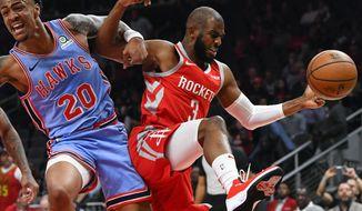 Atlanta Hawks forward John Collins (20) and Houston Rockets guard Chris Paul vie for a rebound during the first quarter of an NBA basketball game Tuesday, March 19, in Atlanta. (AP Photo/John Amis)