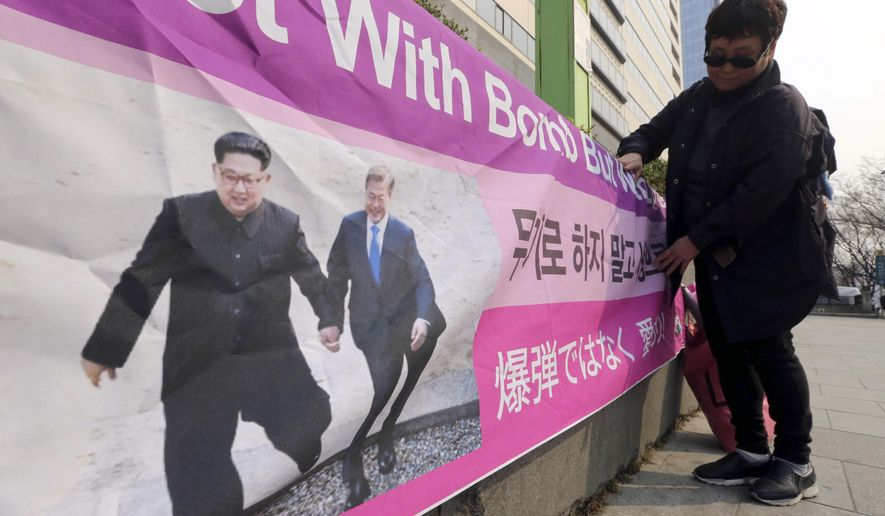 "A woman displays a banner showing a photo of North Korean leader Kim Jong Un and South Korean President Moon Jae-in, right, to wish for peace on the Korean Peninsula, in Seoul, South Korea, Tuesday, March 19, 2019. International journalists' organizations have expressed concern over South Korea's press freedoms after the country's ruling party singled out a Bloomberg reporter over what it claimed was a ""borderline treacherous"" article insulting Moon, resulting in threats to the reporter's safety. (AP Photo/Ahn Young-joon)"