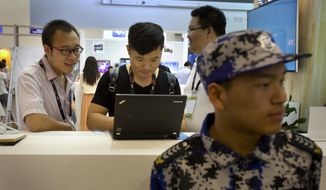 In this April 29, 2015, file photo, visitors use a laptop computer at a display booth as a security guard stands nearby at the Global Mobile Internet Conference in Beijing. (AP Photo/Mark Schiefelbein, File)