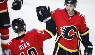 Calgary Flames' Johnny Gaudreau, right, celebrates his goal with teammate Derek Ryan during the first period of an NHL hockey game in Calgary, Alberta, Tuesday, March 19, 2019. (Jeff McIntosh/The Canadian Press via AP)