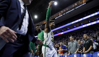 Boston Celtics' Marcus Smart gestures to the crowd as he is escorted off the court after committing a flagrant foul against Philadelphia 76ers' Joel Embiid during the second half of an NBA basketball game Wednesday, March 20, 2019, in Philadelphia. Philadelphia won 118-115. (AP Photo/Matt Slocum)