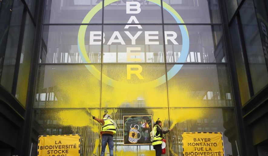 French activists of Attac spray-paint the Paris headquarters of Bayer AG to protest its production of environment-damaging pesticides in la Garenne Colombes, suburb of Paris, Thursday, March 14, 2019. Germany-based Bayer is also under fire from environmental activists in Europe and the U.S. for production of weed killer Roundup by its subsidiary Monsanto. Roundup's key ingredient glyphosate has been blamed for health problems including cancer. (AP Photo/Francois Mori)
