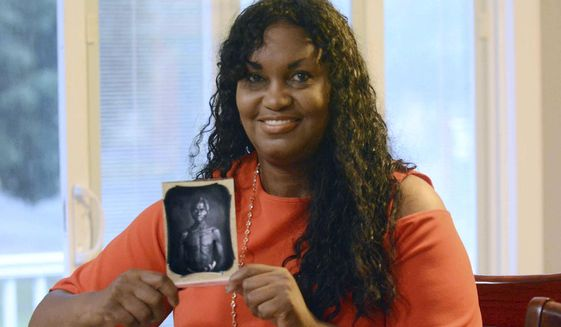 In this July 17, 2018, photo, Tamara Lanier holds an 1850 photograph of Renty, a South Carolina slave who Lanier said is her family's patriarch, at her home in Norwich, Conn. The portrait was commissioned by Harvard biologist Louis Agassiz, whose ideas were used to support the enslavement of Africans in the United States. Lanier filed a lawsuit on Wednesday, March 20, 2019 in Massachusetts state court, demanding that Harvard turn over the photo and pay damages. (John Shishmanian/The Norwich Bulletin via AP)