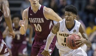 FILE - In this Jan. 27, 2018, file photo, Murray State's Ja Morant (12) moves the ball past Eastern Kentucky's Nick Mayo (10) during the second half of an NCAA college basketball game in Murray, Ky. Murray State point guard Ja Morant is future NBA lottery pick. Marquette point guard Markus Howard is the Big East player of the year. Two of the top-10 scorers in the country meet in a 5-12 NCAA Tournament game in the West Region. (Ryan Hermens/The Paducah Sun via AP, File)