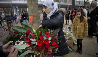 Women representing Utrecht's Muslim community lay a wreath at a makeshift memorial for the victims of a shooting incident in a tram in Utrecht, Netherlands, Tuesday, March 19, 2019. A gunman killed three people and wounded others on a tram in the central Dutch city of Utrecht Monday March 18, 2019. (AP Photo/Peter Dejong)