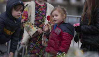 Children lay flowers at a makeshift memorial site for the victims of a shooting incident in a tram in Utrecht, Netherlands, Tuesday, March 19, 2019. A gunman killed three people and wounded others on a tram in the central Dutch city of Utrecht Monday March 18, 2019. (AP Photo/Peter Dejong)