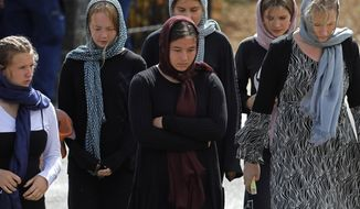 Mourners leave the cemetery after the burial service of the body of a victim of the Friday March 15 mosque shootings at the Memorial Park Cemetery in Christchurch, New Zealand, Thursday, March 21, 2019. (AP Photo/Vincent Yu)