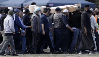 Mourners carry the body of a victim of the Friday, March 15, mosque shootings for burial at the Memorial Park Cemetery in Christchurch, New Zealand, Wednesday, March 20, 2019. New Zealand Police Commissioner Mike Bush says he believes police officers stopped the gunman who killed 50 people at two mosques on his way to another attack. (AP Photo/Mark Baker)
