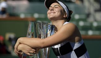 FILE - In this Sunday, March 17, 2019, file photo, Bianca Andreescu, of Canada, smiles as she hugs her trophy after defeating Angelique Kerber, of Germany, in the women's final at the BNP Paribas Open tennis tournament, in Indian Wells, Calif. Roger Federer has won one trophy so far in 2019, which puts him in a tie for the ATP lead, with 18 other players. That same sort of unprecedented parity is going on in the WTA, with 13 different champions from 13 tournaments. (AP Photo/Mark J. Terrill, File)
