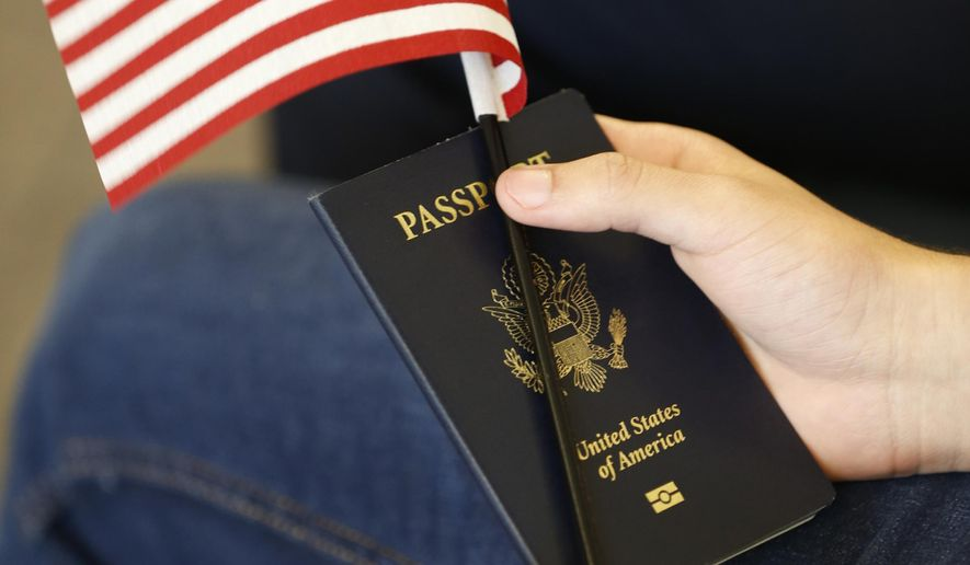 In this Aug. 30, 2018, file photo, a new citizens holds an American flag and passport during a naturalization ceremony at the U.S. Citizenship and Immigration Services Kendall Field Office in Miami.  (AP Photo/Wilfredo Lee, File) **FILE**
