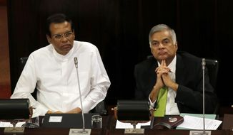 FILE- In this Oct. 3, 2017, file photo, Sri Lankan President Maithripala Sirisena, left, and Prime Minister Ranil Wickremesinghe attend a special session held to mark the country's seventieth anniversary of the first parliament of democracy, in Colombo, Sri Lanka. Sirisena has kept his country's internal political rift from spilling over to a UN human rights council meeting this week by abandoning plans to oppose his prime minister's decision to co-sponsor a resolution that would give the island nation more time to address war crime allegations stemming from its long civil war. The co-resolution to be adopted on March 21, 2019 would give Sri Lanka two more years to investigate and prosecute suspects of rights violations. (AP Photo/Eranga Jayawardena, File)