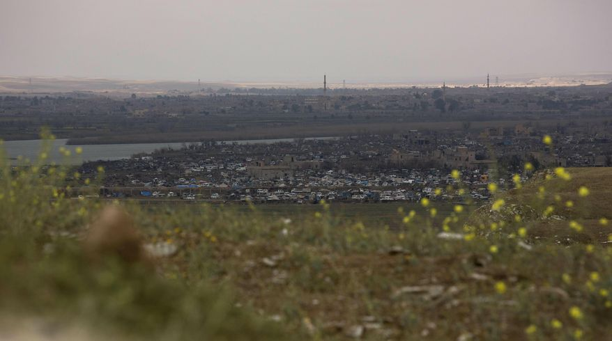 In this Sunday, March 17, 2019, photo, the Islamic State group's last pocket of territory in Baghouz, Syria, as seen from a distance. On Tuesday, a spokesman for U.S.-backed forces fighting IS in Syria says his fighters are in control of an encampment in the village of Baghouz where IS militants have been besieged for months. (AP Photo/Maya Alleruzzo)