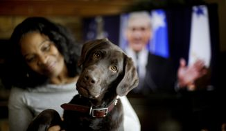 "Alicia Barnett sits with her Chocolate Labrador Retriever named ""Mueller"" in their Kansas City, Kan., home on March 11, 2019. Barnett named the puppy in honor of special prosecutor Robert Mueller, shown on the television in the background, because the dog seemed strong, quiet, proud and a bit mysterious. (AP Photo/Charlie Riedel)"