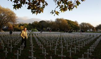 FILE - In this Tuesday, April 25, 2017 file photo, a man walks among the crosses at the field of remembrance following the ANZAC Day dawn service in Christchurch, New Zealand. ANZAC Day is held annually commemorating the April 25, 1915, landings in Gallipoli, the first major military action fought by the Australian and New Zealand Army Corps during World War I. (AP Photo/Mark Baker, File)