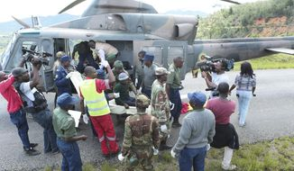 Soldiers and paramedics carry injured survivors from a helicopter in Chimanimani about 600 kilometres south east of Harare, Zimbabwe, Tuesday March, 19, 2019.  According to the government, Cyclone Idai has killed more than 100 people in Chipinge and Chimanimani and according to residents the figures could be higher because the hardest hit areas are still inaccessible.  Some hundreds are dead, many more are missing, and some thousands at risk from the massive flooding throughout the region of Mozambique, Malawi and Zimbabwe caused by Cyclone Idai.(AP Photo/Tsvangirayi Mukwazhi)