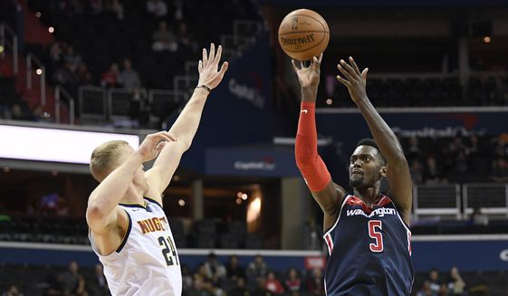 Washington Wizards forward Bobby Portis (5) shoots against Denver Nuggets forward Mason Plumlee (24) during the second half of an NBA basketball game Thursday, March 21, 2019, in Washington. The Nuggets won 113-108. (AP Photo/Nick Wass)