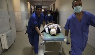 Hospital staff move a wounded victim to the emergency ward in Kabul, Afghanistan, Thursday, March 21, 2019. An Afghan official says three explosions have struck near a Shiite shrine and cemetery in western Kabul as people gathered there to mark the holiday of Nowruz, the Persian New Year. (AP Photo/Rahmat Gul)