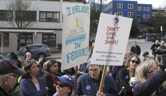 In this photo taken Wednesday March 20, 2019, a group gathered in front of the Alaska Capitol, some carrying signs, in support of the Alaska Marine Highway System in Juneau, Alaska. Gov. Mike Dunleavy's administration has proposed big cuts as it seeks options for reshaping the ferry system, which is an important mode of transport for many coastal communities. (AP Photo/Becky Bohrer)