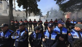 Police officers stand guard during an anti-government rally in Tirana, Albania, Thursday, March 21, 2019. Thousand opposition protesters have gathered in front of Albania's parliament building calling for the government's resignation and an early election. Rally is part of the center-right Democratic Party-led opposition's protests over the last month accusing the leftist Socialist Party government of Prime Minister Edi Rama of being corrupt and linked to organized crime. (AP Photo/ Hektor Pustina)