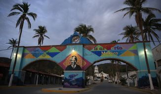 A mural of Nelson Mandela, who spent many of his imprisoned years in an island prison in South Africa, adorns a gate in front of the dock where prison staff and inmates arrive in Navy boats to the now closed Islas Maria penal colony located off Mexico's Pacific coast, at dawn Sunday, March 17, 2019. Islas Marias was the last of its kind, the final of a half dozen island penal colonies that were scattered around Latin America. (AP Photo/Rebecca Blackwell)