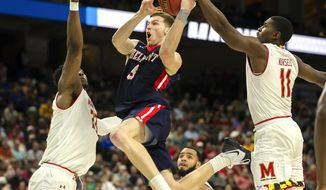Belmont 's Dylan Windler, center, goes to the basket between Maryland 's Bruno Fernando, left, and Darryl Morsell (11) during the second half of the first round men's college basketball game in the NCAA Tournament in Jacksonville, Fla. Thursday, March 21, 2019. (AP Photo/Stephen B. Morton)
