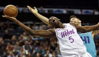Minnesota Timberwolves center Gorgui Dieng (5), of Senegal, battles Charlotte Hornets center Willy Hernangomez for a rebound in the first half of an NBA basketball game in Charlotte, N.C., Thursday, March 21, 2019. (AP Photo/Nell Redmond)
