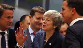 British Prime Minister Theresa May, center, speaks with Dutch Prime Minister Mark Rutte, right, and Luxembourg's Prime Minister Xavier Bettel, left, during a round table meeting at an EU summit in Brussels, Thursday, March 21, 2019. British Prime Minister Theresa May is trying to persuade European Union leaders to delay Brexit by up to three months, just eight days before Britain is scheduled to leave the bloc. (AP Photo/Frank Augstein)