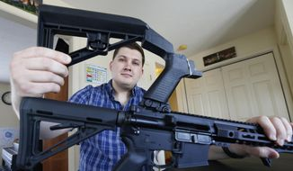 In this March 15, 2019, file photo, Ryan Liskey displays a bump stock on top of his AR-15 at his home in Harrisonburg, Va. The ban on bump stocks is just a few days away and owners of the devices like Liskey are trying to figure out what to do. (AP Photo/Steve Helber)