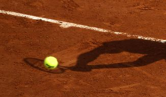 FILE - In this May 28, 2016 file photo, a player's shadow is pictured as he returns the ball during the French Open tennis tournament at the Roland Garros stadium, in Paris. Judicial officials say Thursday March 21, 2019 that French police have questioned another batch of players about their links to an alleged match-fixing syndicate suspected of paying out hundreds of thousands of euros (dollars) to fix low-level tennis matches. (AP Photo/Alastair Grant, File)