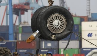 In this Saturday, Nov. 3, 2018, file photo, a crane moves a pair of wheels recovered from the Lion Air jet that crashed into the Java Sea for further investigation at Tanjung Priok Port in Jakarta, Indonesia.  Indonesia's transport safety board chair said during a press conference, Thursday, March 21, 2019, that a third pilot was in the cockpit of penultimate Lion Air flight before the crash. (AP Photo/Achmad Ibrahim, File)