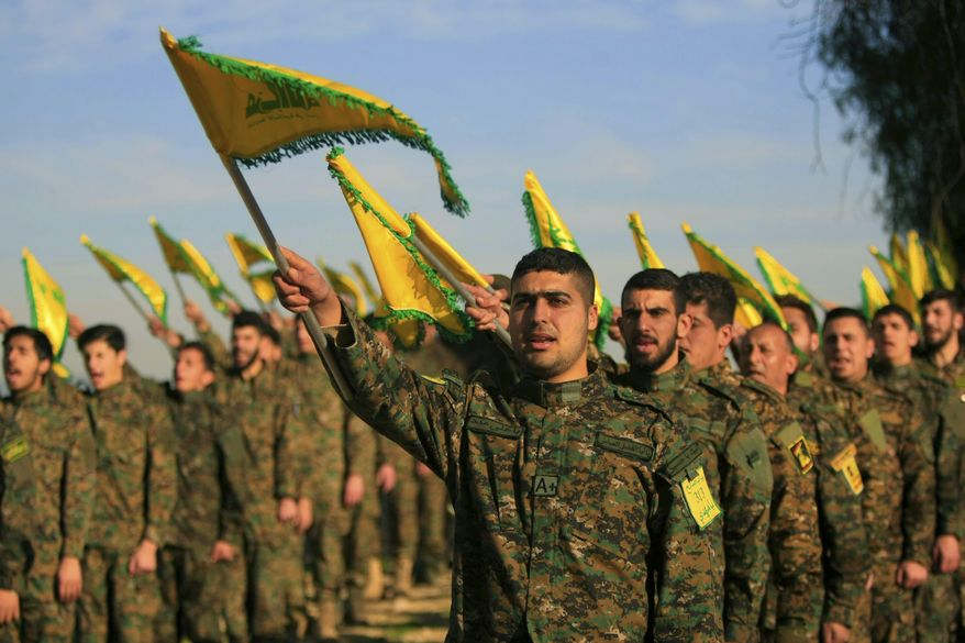 In this Feb. 13, 2016 file photo, Hezbollah fighters hold flags as they attend the memorial of their slain leader Sheik Abbas al-Mousawi, who was killed by an Israeli airstrike in 1992, in Tefahta village, south Lebanon.  (AP Photo/Mohammed Zaatari, File) **FILE**