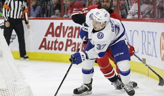 Tampa Bay Lightning's Yanni Gourde (37) chases the puck with Carolina Hurricanes' Calvin de Haan (44) during the first period of an NHL hockey game in Raleigh, N.C., Thursday, March 21, 2019. (AP Photo/Gerry Broome)