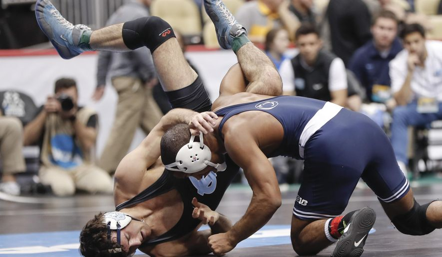 Penn State'a Mark Hall, right, lifts North Carolina's Devin Kane in their 174 lbs. match in the first round of the NCAA college wrestling championship, Thursday, March 21, 2019, in Pittsburgh. (AP Photo/Keith Srakocic)