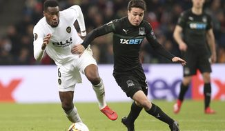 Valencia's Geoffrey Kondogbia, left, and Krasnodar's Mauricio Pereyra challenge for the ball during the Europa League round of 16, second leg soccer match between FC Krasnodar and Valencia at the Krasnodar Stadium in Krasnodar, Russia, Thursday, March 14, 2019. (AP Photo/Vitaliy Timkiv)