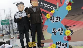 "Protesters wearing masks of U.S. President Donald Trump and North Korean leader Kim Jong Un stand near the map of Korean Peninsula during a rally demanding the denuclearization of the Korean Peninsula and peace treaty near the U.S. embassy in Seoul, South Korea, Thursday, March 21, 2019. The Korean Peninsula remains in a technical state of war because the 1950-53 Korean War ended with an armistice, not a peace treaty. More than 20 protesters participated at a rally and also demanding the end the Korean War and to stop the sanction on North Korea. The letters read ""Peace and Unification."" (AP Photo/Lee Jin-man)"