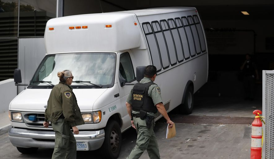 In this Tuesday, March 19, 2019, file photo, a van carrying asylum seekers from the border is escorted by security personnel as it arrives to immigration court, in San Diego. Scheduling glitches led an immigration judge to deny the Trump administration's request to order four Central American migrants deported because they failed to show for initial hearings Wednesday, March 20, 2019, dealing a setback to a highly touted initiative to make asylum seekers wait in Mexico while their cases wind through U.S. immigration courts. (AP Photo/Gregory Bull, File)